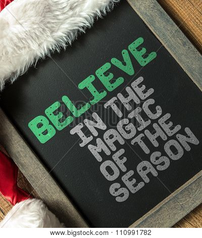 Believe in the Magic of the Season written on blackboard with santa hat