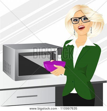 businesswoman using microwave to heat homemade food