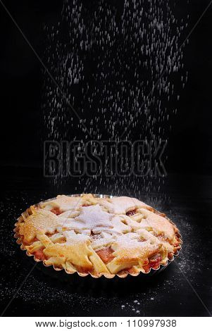 Apple Pie And Falling Powdered Sugar On Black Table