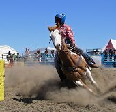stock photo of barrel racing  - a cowgirl competing in the barrel race - JPG