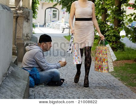 Beggars and wealthy woman with shopping bags