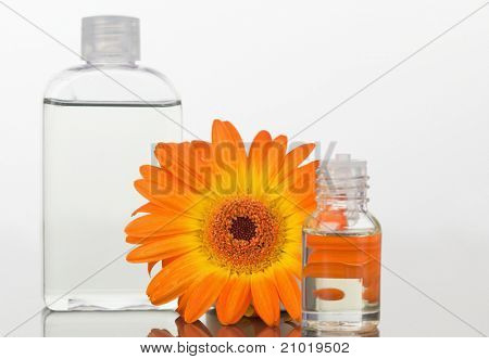 A glass phial and an orange flower with a glass flask against white background