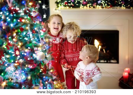 Children At Christmas Tree. Kids At Fireplace On Xmas Eve Poster ID ...