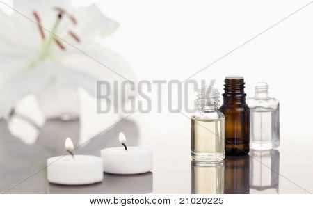 White orchid with lighted white candles and small phials th camera focus on the objects