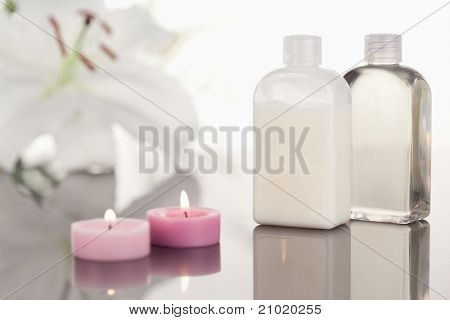 White orchid  glass phials and lighted pink candles