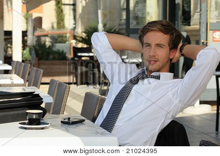young man wearing a suit and tie, relaxing on a terrace at breakfast time