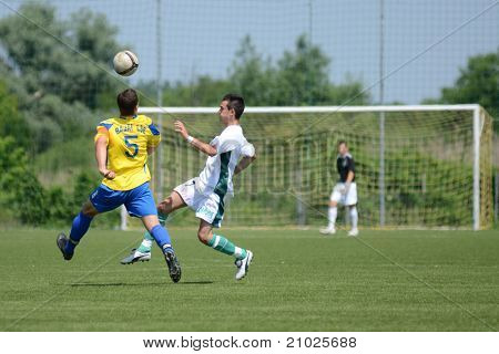 KAPOSVAR, HUNGARY - JUNE 11: Tamas Nagy (in yellow) in action at the Hungarian National Championship under 13 game between Kaposvari Rakoczi FC and Bajai LSE on June 11, 2011 in Kaposvar, Hungary.