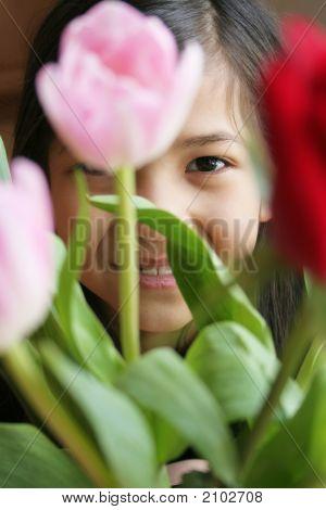 Child Peeking Through The Tulips