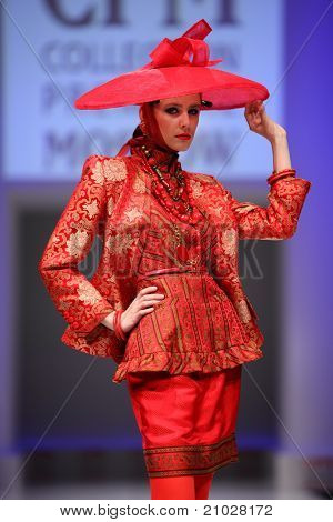 MOSCOW - FEBRUARY 22: A model wears a red suit and hat from Slava Zaytzev and walks the catwalk in Collection Premiere Moscow, fashion industry platform of IGEDO Company, on February 22, 2011 in Moscow, Russia.