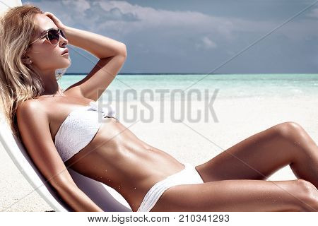 poster of fashion photo of beautiful tanned woman with blond hair in elegant white bikini relaxing on white chair in tropical island with perfect beach.