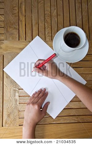Female hand with pencil writing on a white sheet of paper
