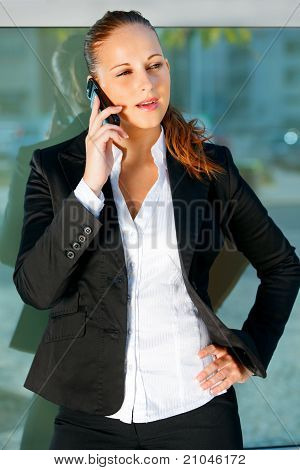 Concentrated modern business woman talking on mobile near office building