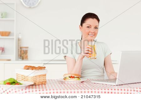 Smiling Woman Relaxing On Her Laptop While Drinking A Glass Of Orange Juice