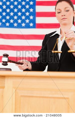 Portrait Of A Cute Judge Knocking A Gavel And Holding Scales Of Justice