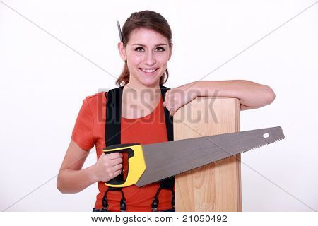 Woman sawing a wooden floor board