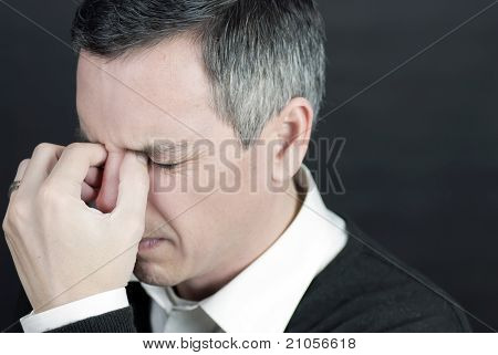Man With Migraine Holds Bridge Of Nose