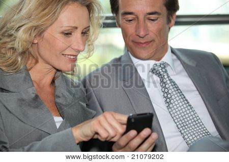 Pair of executives looking at something on a cellphone