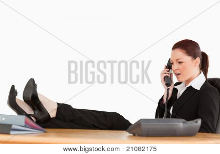 Unhappy business woman on the phone in her office against a white background