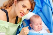 foto of ares  - Caring young mother hugging sitting in stroller crying baby - JPG
