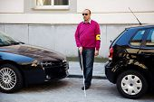 stock photo of blind man  - A blind man walks with a cane on a street - JPG