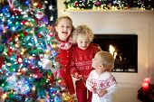 Children At Christmas Tree. Kids At Fireplace On Xmas Eve poster