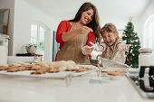 Mother And Daughter Having Fun While Making Christmas Cookies. poster