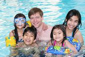 stock photo of floaties  - Father and his four children enjoying their swimming time in the pool - JPG