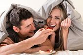 Funny young couple in love eating bread with strawberry jam during breakfast in bed poster