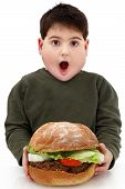 foto of obese  - Hungry obese child with giant hamburger over white - JPG