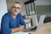 Middle-aged man working from home-office on laptop poster