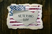high-angle shot of a piece of paper in the shape of the United States with the text veterans day wri poster