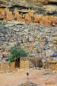 stock photo of dogon  - A small child playing in front of ancient Dogon and Tellem houses at the base of the Bandiagara escarpment in Mali - JPG