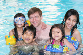stock photo of swimming pool family  - Father and his four children enjoying their swimming time in the pool - JPG