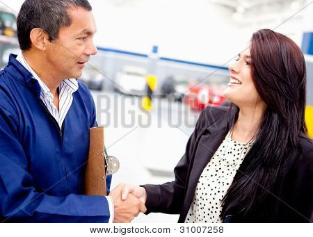 Woman at the mechanic handshaking after a good service
