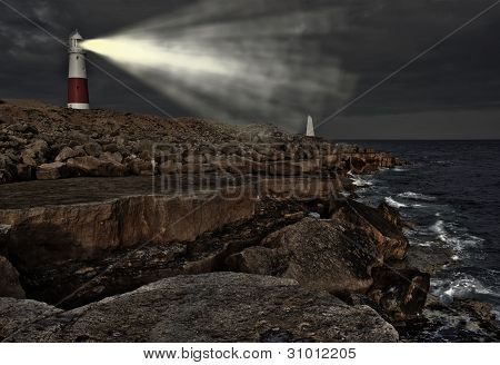 Victorian Lighthouse On Promontory Of Rocky Cliffs With Beam Alight At Night