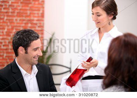 Waitress serving a couple wine