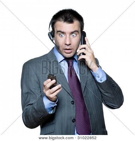 Portrait of surprised businessman wearing headset and using mobile phone busy with multiple telephone in studio isolated white background