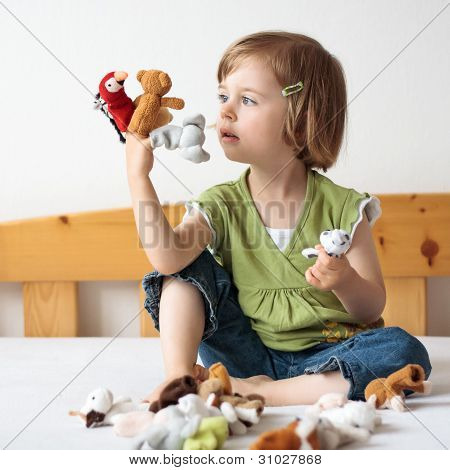 Sitting Young Girl Playing With Small Puppets