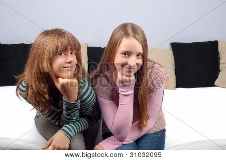 Two pretty teenage girls sitting on the bed and smiling