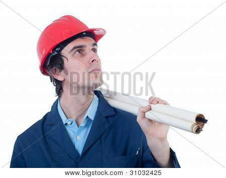 Portrait of engineer wearing blue shirt, red helmet, blue working coat and holding blueprint rolls i