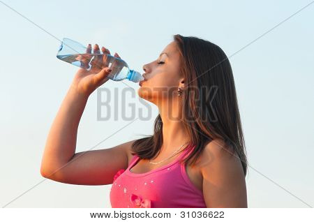 Beautiful young girl drinks bottled water outdoor
