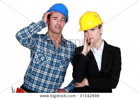female architect looking annoyed and foreman by her side