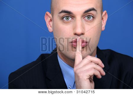 Bald businessman making shush gesture