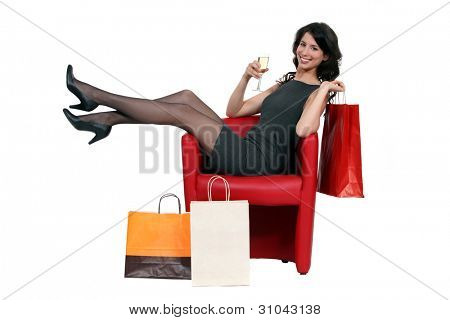 Sexy woman posing with her shopping bags and drinking a glass of wine