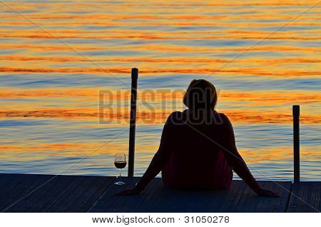 Woman with glass of wine on dock