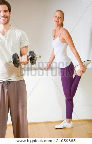 Man Lifting Dumbbell And Woman Stretching In Gym