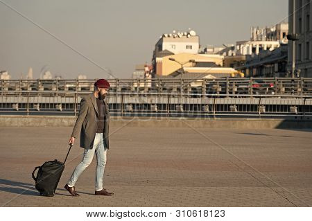 poster of Adjust Living In New City. Carry Travel Bag. Man Bearded Hipster Travel With Luggage Bag On Wheels.