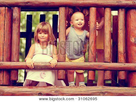 Foto in Sepia-Tönen von Bruder und Schwester auf dem Spielplatz spielen