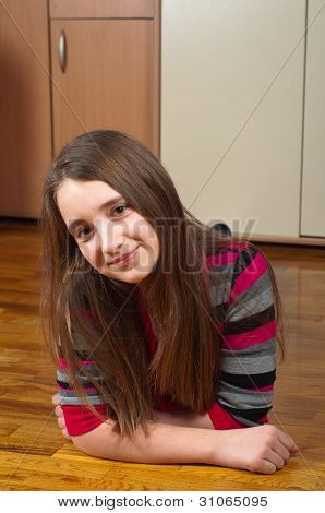 Cute smiling teenage girl lying on the wooden floor of her room