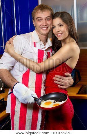 Guapo, freír huevos para su novia en la cocina